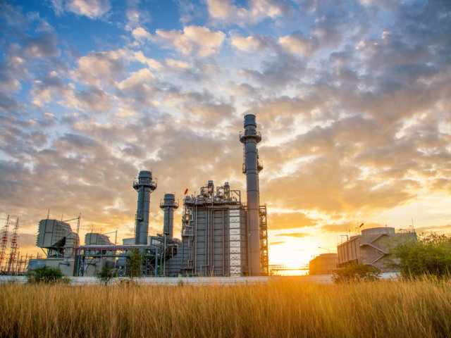 Turbine electric power plant building during sunset time on nature background